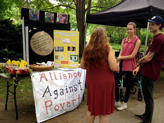 People at the Alliance Against Poverty booth