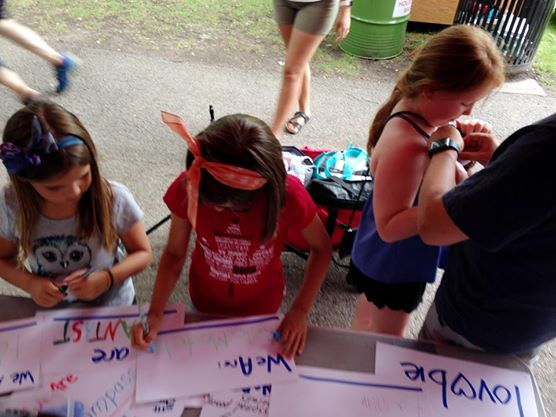 Children writing on signs for the We Are project
