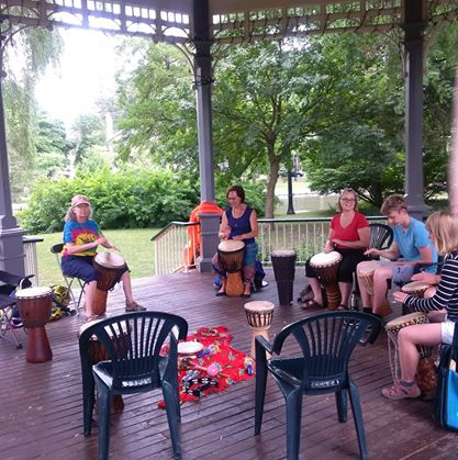 People in the Victoria Park gazebo playing Djembe drums