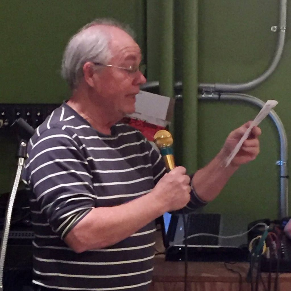 Peter Jantzi reads from a paper while holding a microphone