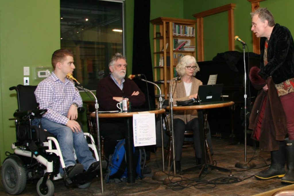David Kuhn, Allan Strong, and Elizabeth Clarke seated at the microphones; an audience member on stage asking questions