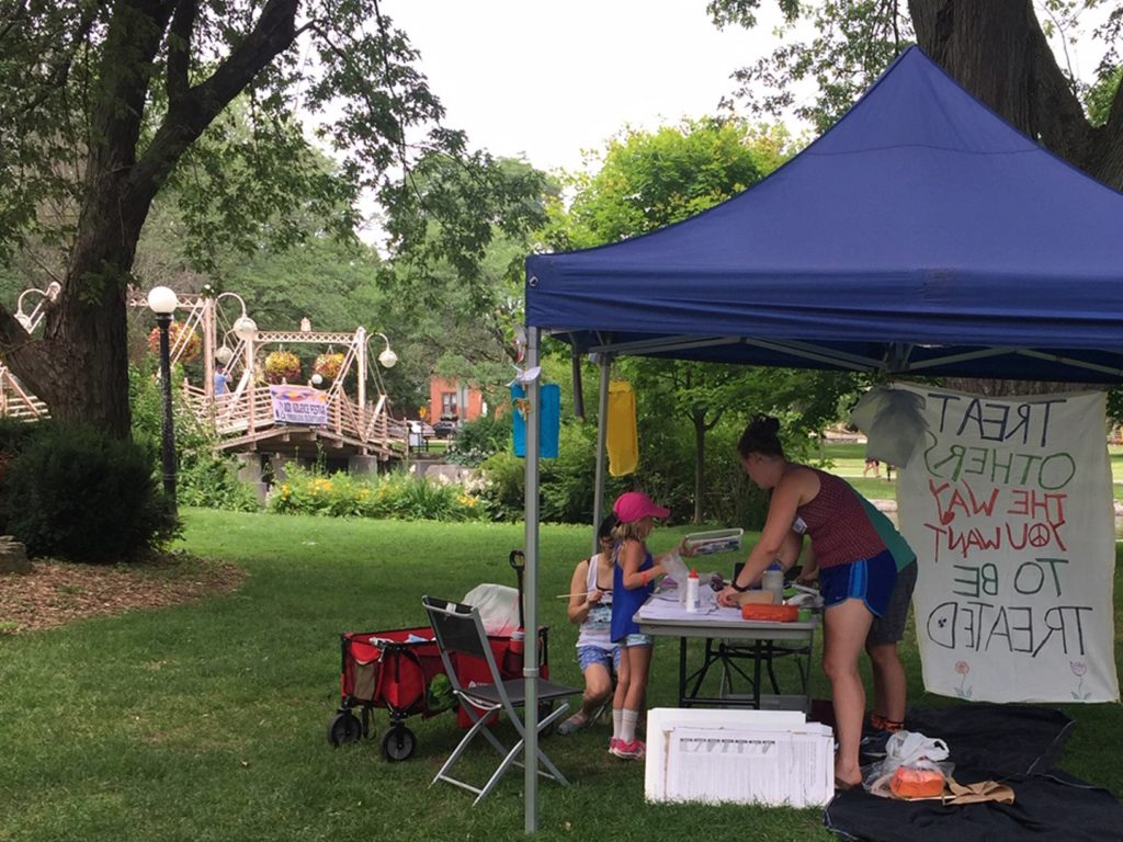 A tent with arts and crafts supplies, kids at the table, and adults behind