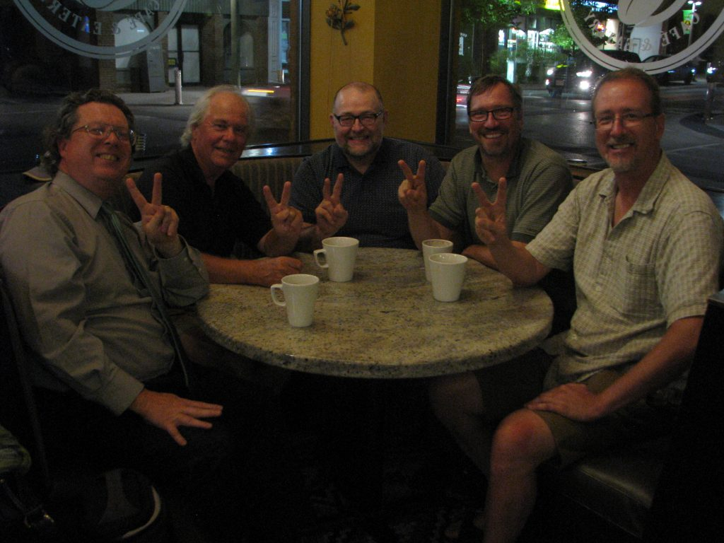 Five people giving a peace sign