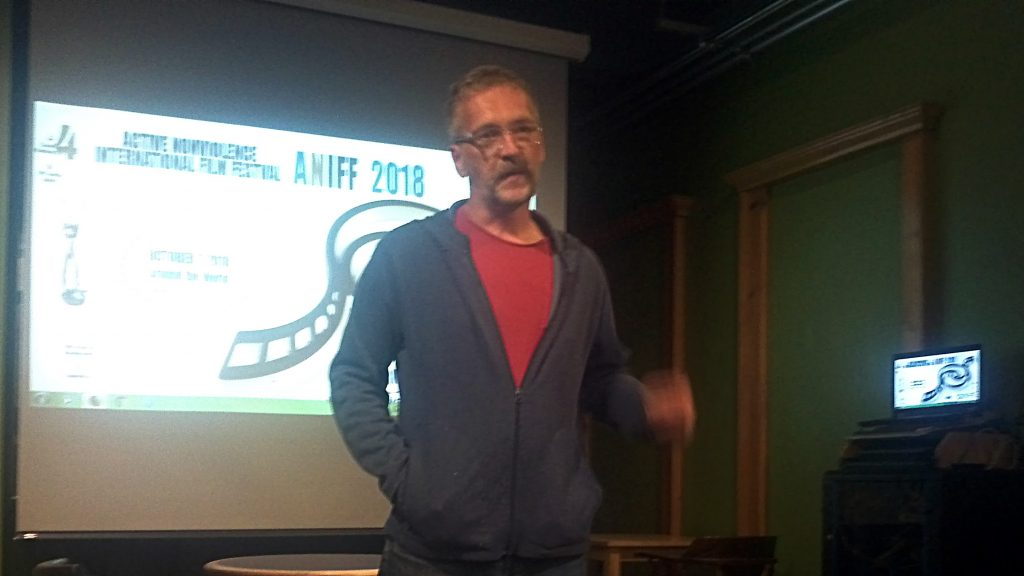 Matt Albrecht stands in front of a movie screen showing the ANIFF logo