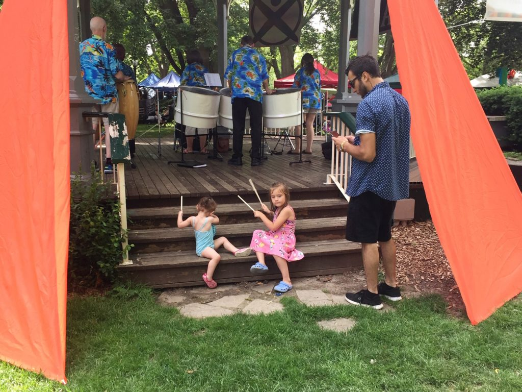 Children sitting on the steps to the Gazebo with drumsticks while their Dad looks on, with the Acoustic Steel Band in the background