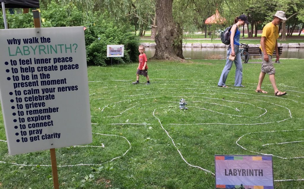 People walking along the labryrinth rope with a sign on labyrinths to the left